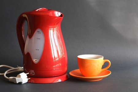 electric tea kettle: Nice modern red electric kettle near cup of tea on dark background