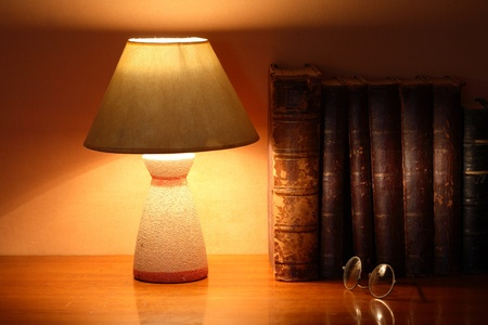 reading lamp: Luminous desk lamp near ancient books on ginger background with beam of light
