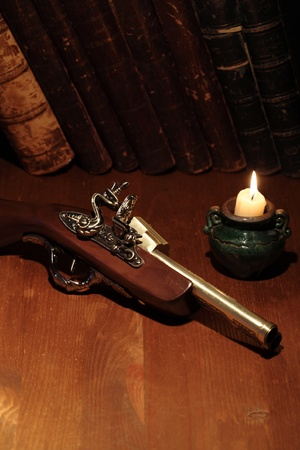 gunfire: Lighting candle near ancient pistol on wooden surface with old books