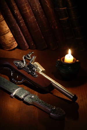 candlestick: Lighting candle near ancient pistol and dagger on wooden surface with old books Stock Photo