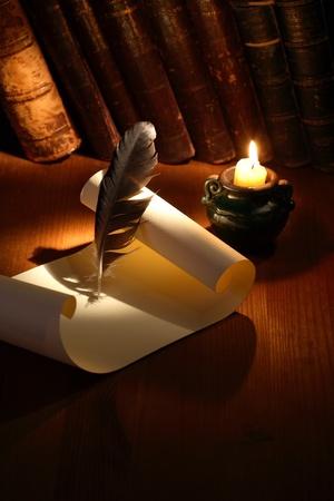 Weinlese-Stillleben mit Scroll-und Federkiel auf hölzernen Oberfläche in der Nähe Beleuchtung Kerze