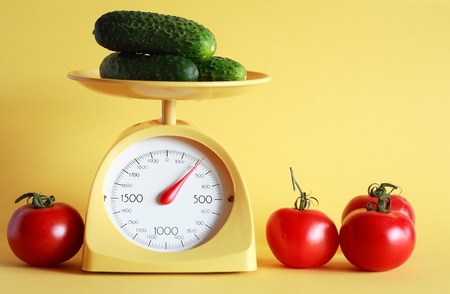 Still life with modern kitchen scale and vegetables on yellow background photo