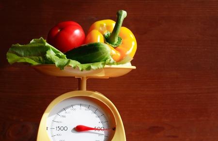 balanza en equilibrio: Bodeg�n con escala de cocina moderna y verduras sobre fondo de madera