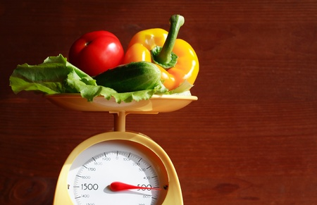 Still life with modern kitchen scale and vegetables on wooden background