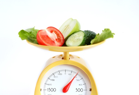 Sliced fruits and vegetables on kitchen scale