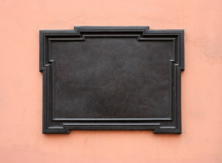 Blank cast-iron plaque on stone wall. Add your own text or image. Clipping path is included Stock Photo