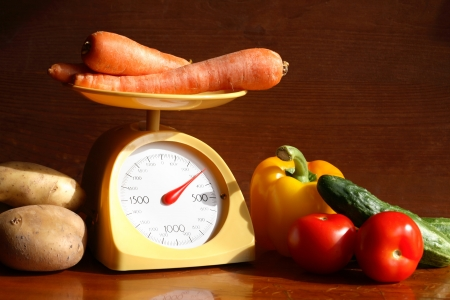 Still life with modern kitchen scale and vegetables on wooden background photo