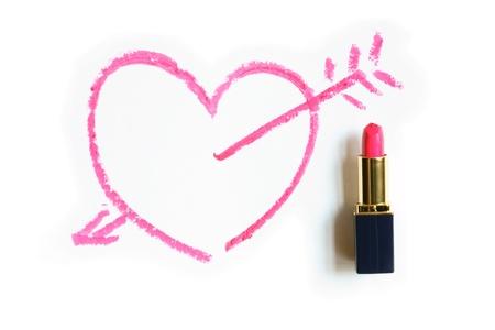 Red Lippenstift bemalt nahe Herz und Liebe Pfeil auf weißem Hintergrund