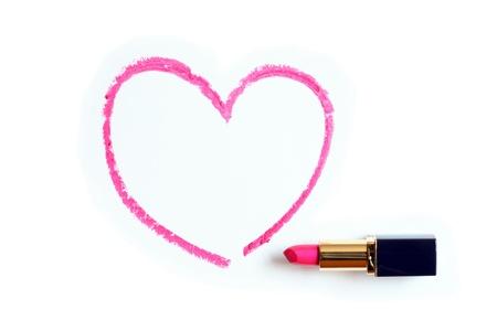Red Lippenstift bemalt Nähe Herzform auf weißem Hintergrund