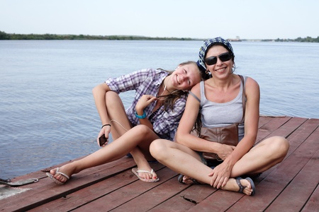 daugther: Beauty smiling teen girl and her mother sitting on wooden moorage near river