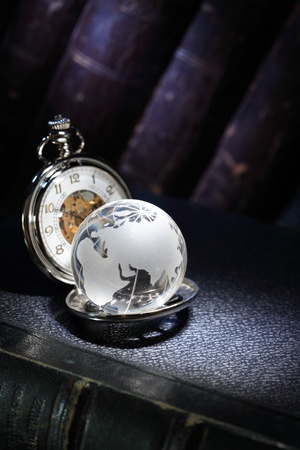 Closeup of glass globe and vintage pocket watch on dark background with old books