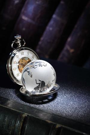 Nahaufnahme der Glaskugel und Vintage-Taschenuhr auf dunklem Hintergrund mit alten Bücher