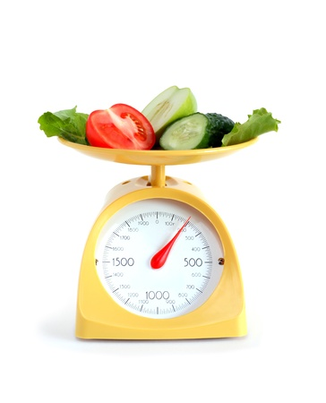 weight scale: Sliced fruits and vegetables on kitchen scale. Isolated on white with clipping path Stock Photo