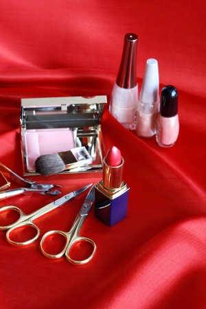 Still life with cosmetics set on red silk photo