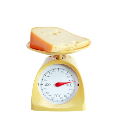 Piece of cheese lying on nice yellow kitchen scale. photo