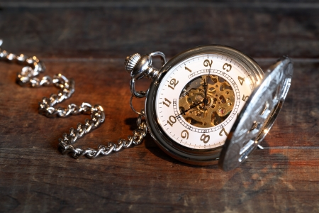 pocket watch: Vintage pocket watch with open lid and chain on wooden surface Stock Photo