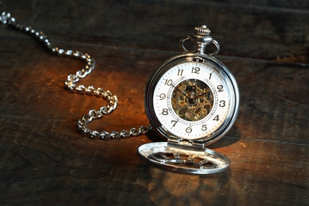 Vintage pocket watch with open lid and chain on wooden surface photo