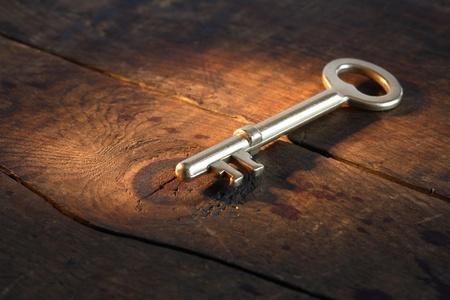 Closeup of vintage goldenen Schlüssel liegen auf alten hölzernen Oberfläche mit Lichtstrahl