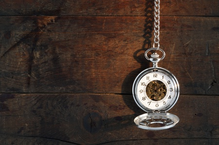 Time concept. Stylish pocket watch hanging with chain against old wooden background