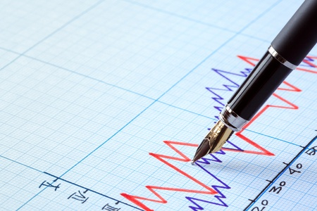 Business concept. Closeup of fountain pen on graph paper with diagram photo