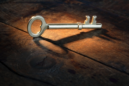 Closeup of vintage golden key standing on old wooden surface with beam of light