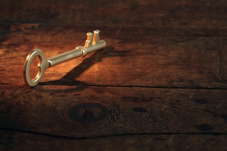 Closeup of vintage golden key standing on old wooden surface with beam of light Stock Photo - 10761772