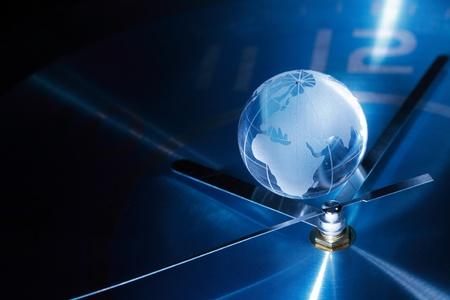 時間の概念。ガラス グローブ青い金属時計の顔の上に横たわるのクローズ アップ