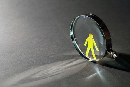 Gelbes Papier Mann in der Nähe Lupe auf dunklem Hintergrund mit Lichtstrahl