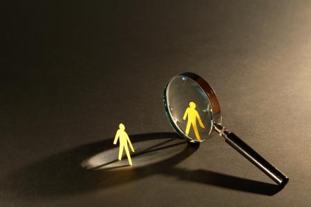 暗い面上の 2 つの小さな紙男性間虫眼鏡に立って 写真素材