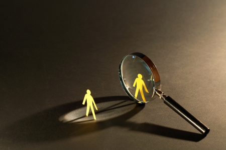 supervision: Magnifying glass standing between two small paper men on dark surface