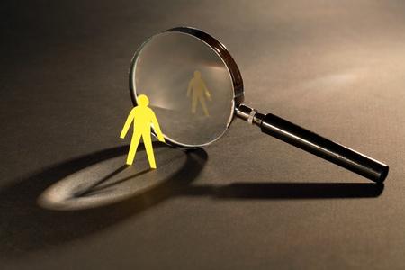 Small yellow paper man standing opposire magnifying glass on dark surface Standard-Bild
