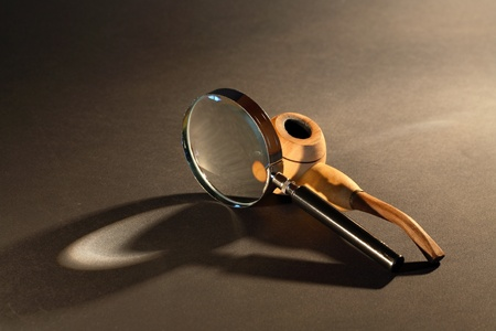 detective agency: Old detective concept. Magnifying glass and tobacco pipe on dark surface