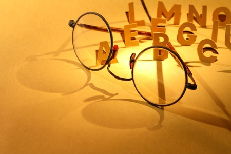 Reading concept. Old spectacles on yellow paper surface with cutting letters photo