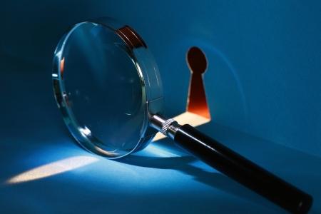 lupa: Špehování koncept. Zvětšovací sklo u klíčové dírky s paprskem světla Reklamní fotografie