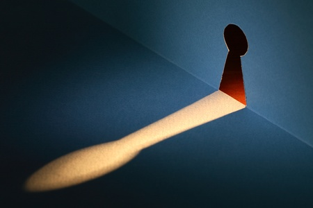 under surveillance: Spying concept. Beam of light through keyhole cutting from paper