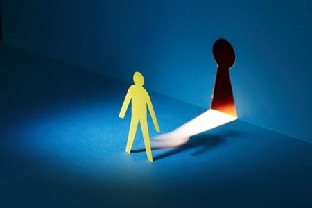 derechos humanos: Espionaje concepto. El hombre de papel amarillo de pie contra el ojo de la cerradura que brilla intensamente
