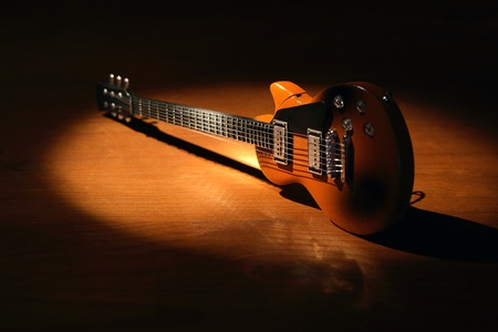 Music concept.Electric guitar on wooden surface under beam of light Stock Photo - 11431858