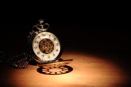 Stylish pocket watch on wooden surface under beam of light Standard-Bild