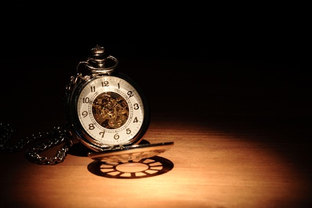 Stylish pocket watch on wooden surface under beam of light Stock Photo