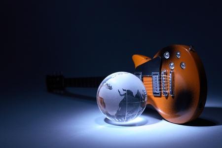 Music concept. Glass globe near electric guitar under beam of light on dark background