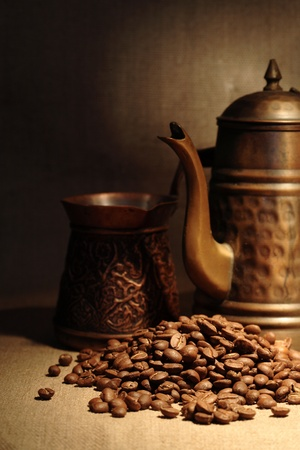 coffeepot: Vintage still life with heap of coffee beans near old copper coffeepot Stock Photo