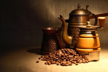 古い銅のコーヒー ポットに近いコーヒー豆のヒープのヴィンテージの静物 写真素材