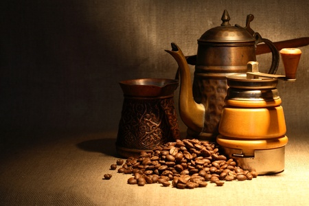 Vintage still life with heap of coffee beans near old copper coffeepot photo