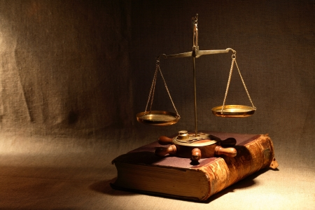 Legislation concept. Old brass weight scale standing on ancient book under beam of light