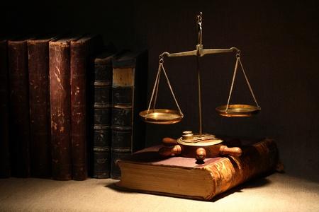 Wetgeving concept. Oude koperen weegschaal en oude boeken onder lichtstraal op donkere achtergrond