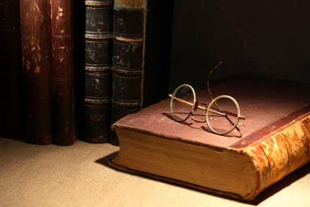 history: Vintage still life with old books and spectacles on canvas surface
