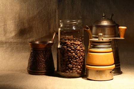 coffeepot: Turkish coffee.Glass jar with coffee beans near old copper coffeepot on canvas background