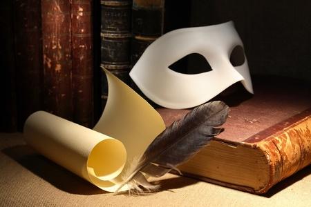 ドラマツルギー概念。クイルおよびスクロール マスクと暗い背景上の古い本の近くのビンテージ静物