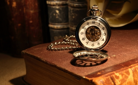Still life with stylish pocket watch on ancient book photo