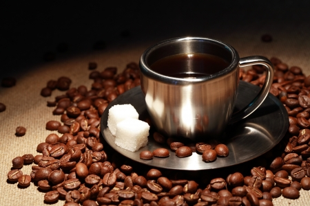 Stylish modern steel cup with sugar and coffee beans on canvas surface Stock Photo